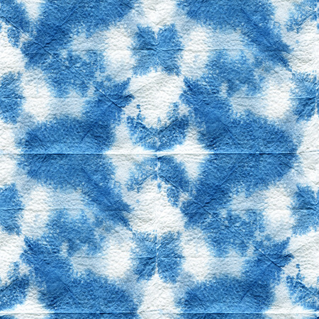 dyeing: Seamless tie-dye pattern of indigo color with a geometrical ornament. Hand painting fabrics - nodular batik. Shibori dyeing.