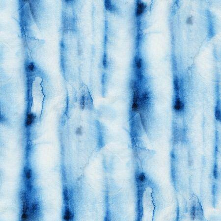Seamless tie-dye pattern of indigo color with vertical stripes. Hand painting fabrics - nodular batik. Shibori dyeing.