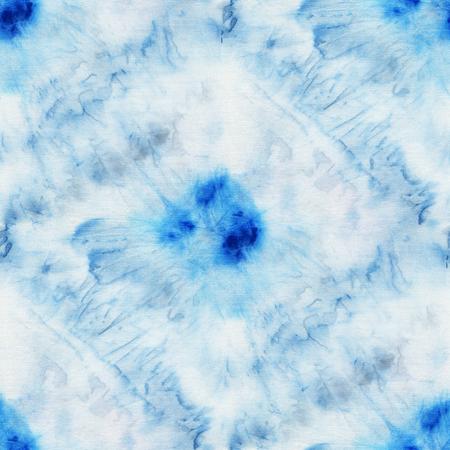 dyeing: Seamless tie-dye pattern of indigo color on white silk. Hand painting fabrics - nodular batik. Shibori dyeing.