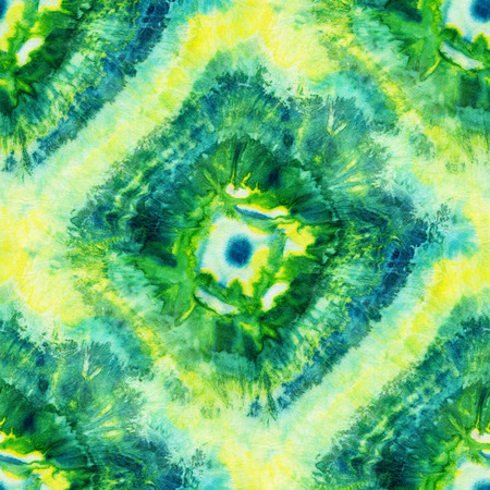 Seamless tie-dye pattern of green and yellow color on white silk. Hand painting fabrics - nodular batik. Shibori dyeing.