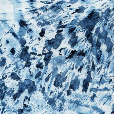 Tie-dye pattern of indigo color on white silk. Hand painting fabrics - nodular batik. Shibori dyeing.