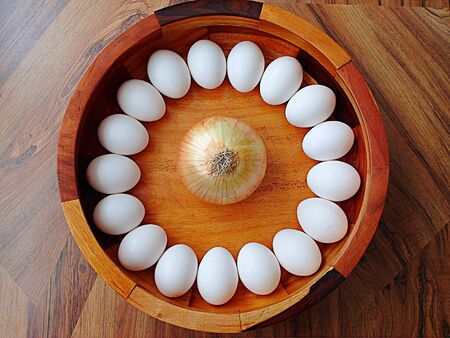 Eggs arranged in a circle with an onion in the center on a wooden surface.