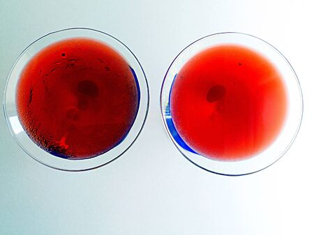 overhead shot of two red martinis on a white background