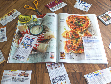 An overhead shot of clipped coupons, scissors and a magaine.