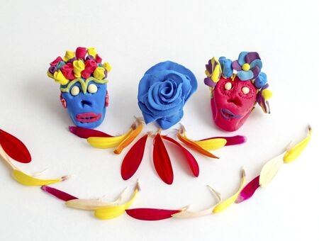 Clay day of the dead sugar skulls with flower petals.