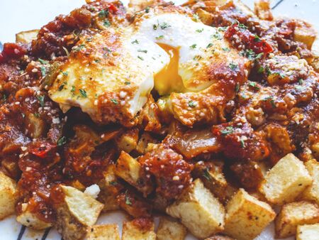Eggs poached in tomato sauce over fried potatoes.