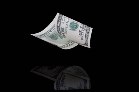 Falling hundred dollar bill on a black background with reflection Stock Photo