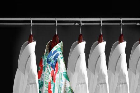 Tropical shirt between white shirts hanging inside a closet Stock Photo - 7557716