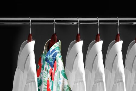 Tropical shirt between white shirts hanging inside a closet Stock Photo