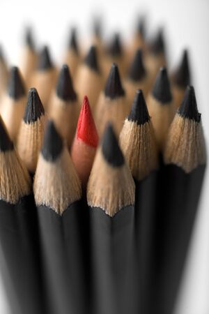 sharpen: A bunch of graphite pencils with one red in the middle