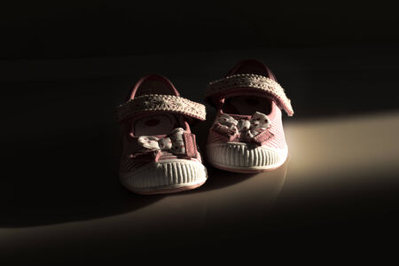 baby shoes: Conceptual image of violence to kids represented with a pair of baby shoes on a dark background