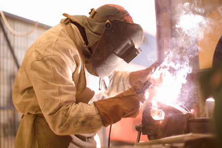 welding mask: Arc welder on work with protective helmet Stock Photo