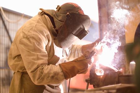 seguridad laboral: Soldador de arco en el trabajo con casco protector Foto de archivo