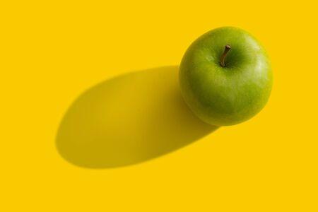 manzana verde: manzana verde con sombra sobre fondo amarillo