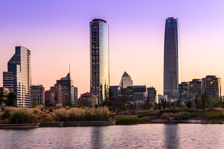 Santiago, Region Metropolitana, Chile - February 13, 2017: Pond at Parque Bicentanario, a park in the wealthy district of Vitacura with the skyline of the modern buildings at the financial district populary know as Sanhattan.