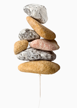 A stack of stones over a pin representing the concept of holding weight.