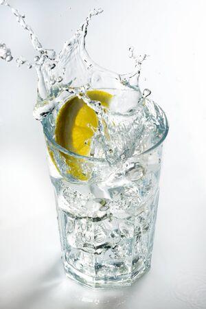 Lemon splashing on a glass against a white background