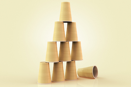 3D rendering of plastic cups stacked in a pyramid with one fallen down representing the concept of failure at teamwork.
