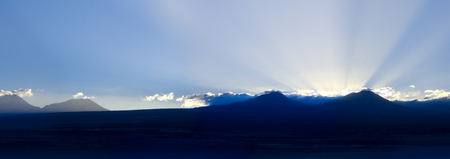 Sunrise behind the Andes Mountain Range, with the Altiplano line (High Andean Plateau) in silhouette, Atacama desert, Chile, South America