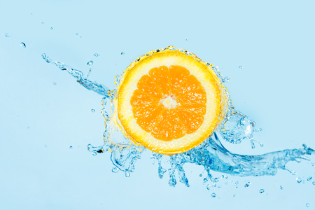 Water splashing in a half orange against a light blue background