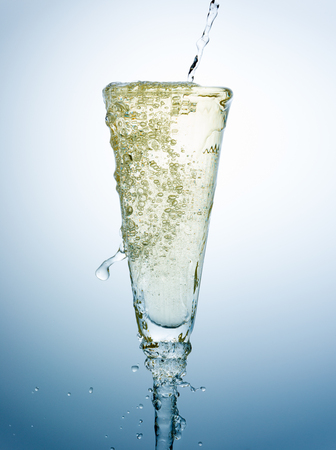 Pouring and overfill of Champagne on a fancy glass against a blue background