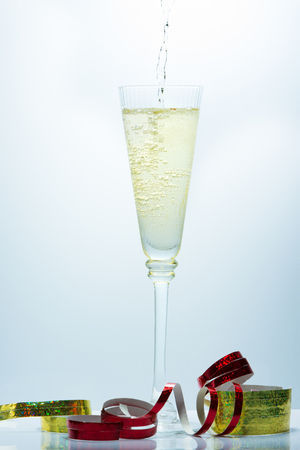 Pouring of Champagne on a fancy glass against a blue background