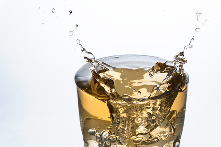 Close up of an ice cube splashing on a glass of Ginger Ale soft drink