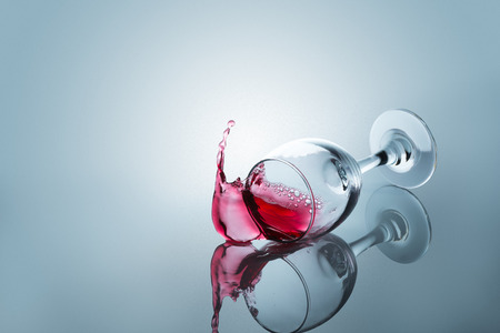Red wine spilled out of a falling glass reflected on the surface Stock Photo