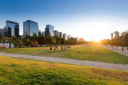 Santiago, Region Metropolitana, Chile - January 17, 2019: People practicing sports at Parque Araucano, the main park in Las Condes district, surrounded by office buildings of Nueva Las Condes business center. Editorial