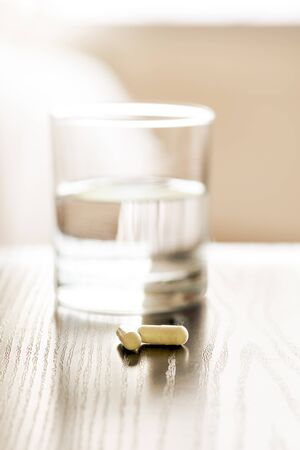 Pills next to a glass of water