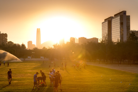 Santiago, Region Metropolitana, Chile - January 17, 2019: People practicing sports at Parque Araucano, the main park in Las Condes district, surrounded by office buildings of Nueva Las Condes business center. Редакционное