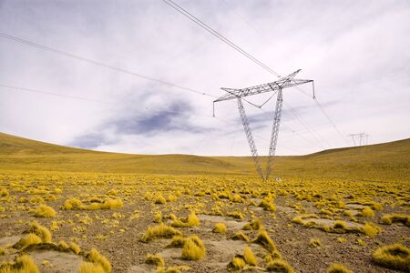 Power lines towers in the Altiplano (high Andean plateau) at 4200 meters over the sea level, Atacama desert, Antofagasta Region, Chile, South America