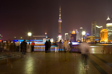 Shanhai, China - November 28, 2008: People at The Bund riverside looking at the skyline of Lujiazui and Pudong with the Oriental Pearl Tower, across the Huangpu river.