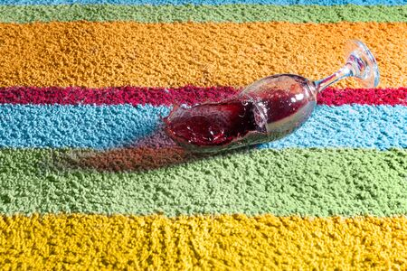 Glass of red wine falling over the carpet Banco de Imagens