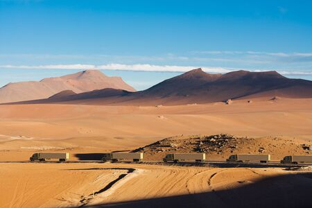 3D rendering of a caravan of cargo trucks crossing an arid desert. Stock Photo