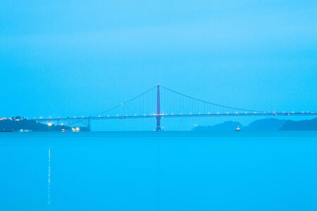 A side view of the Golden Gate Bridge at a blue dawn in San Francisco, California, United States