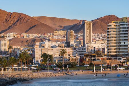 Antofagasta, Region de Antofagasta, Chile - April 19, 2017: Skyline of buildings and people at the boulevard at the side of the beach.