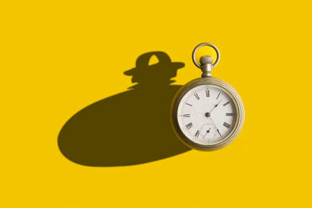 Old pocket clock with a bold shadow in a yellow background Stock fotó