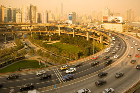 Shanghai, China, Asia - Traffic at the Access / Exit ramp to to Nanpu Bridge and city skyline.