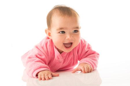 6 month old baby girl crawling on white background. Reklamní fotografie