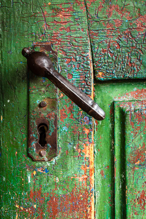 Color picture of an old doorknob on a green door, close-up