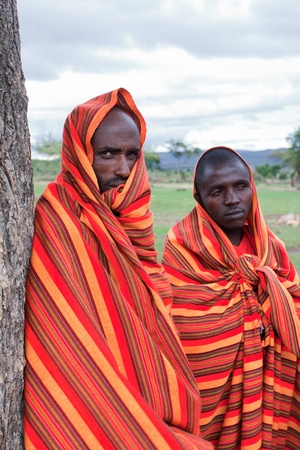 Masai Mara, Kenya - December 28, 2009: Two unidentified African men pose for a portrait on December 28, 2009 in Masai Mara, Kenya. The Masai are a Nilotic ethnic group of semi-nomadic people located in Kenya and Tanzania.