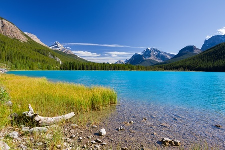 Beautiful Canadian Landscape: Lake with turquoise blue water, Rocky Mountains and Clear Sky. Photo was taken on sunny day of summer in Jasper National Park, Alberta, Canada