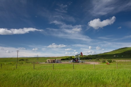 Beautiful landscape with green grass, blue sky and pumpjack  Photo is taken on sunny day of summer in Alberta, Canada   photo