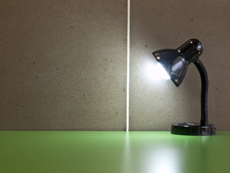 glister: The black table lamp on the green desk in front of cement wall background Stock Photo