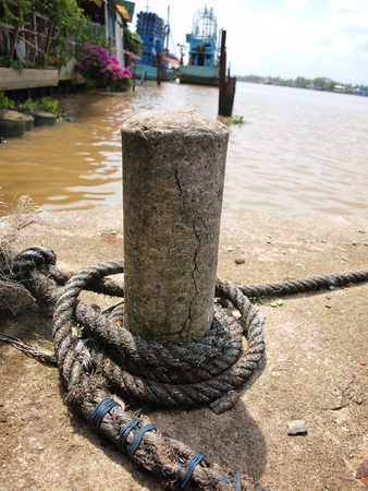 belay: Mooring rope tied to a cement pole on a pier.