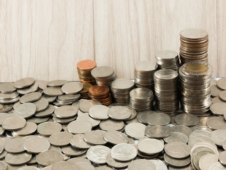 argent: stack of Thai coins(Baht) in wooden wall background