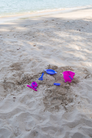 Childrens bright sand play equipment, such as a bucket shovel, a sandpit at the beach. Stock Photo