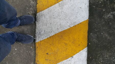 남자들의 다리는 흰색 노란색 라인을 걷고 있으며, 운전을 할 때는 조심해야한다고 경고합니다.