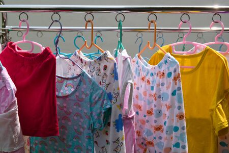 Clothes and childrens dresses in various colors were washed and dried in rows.
